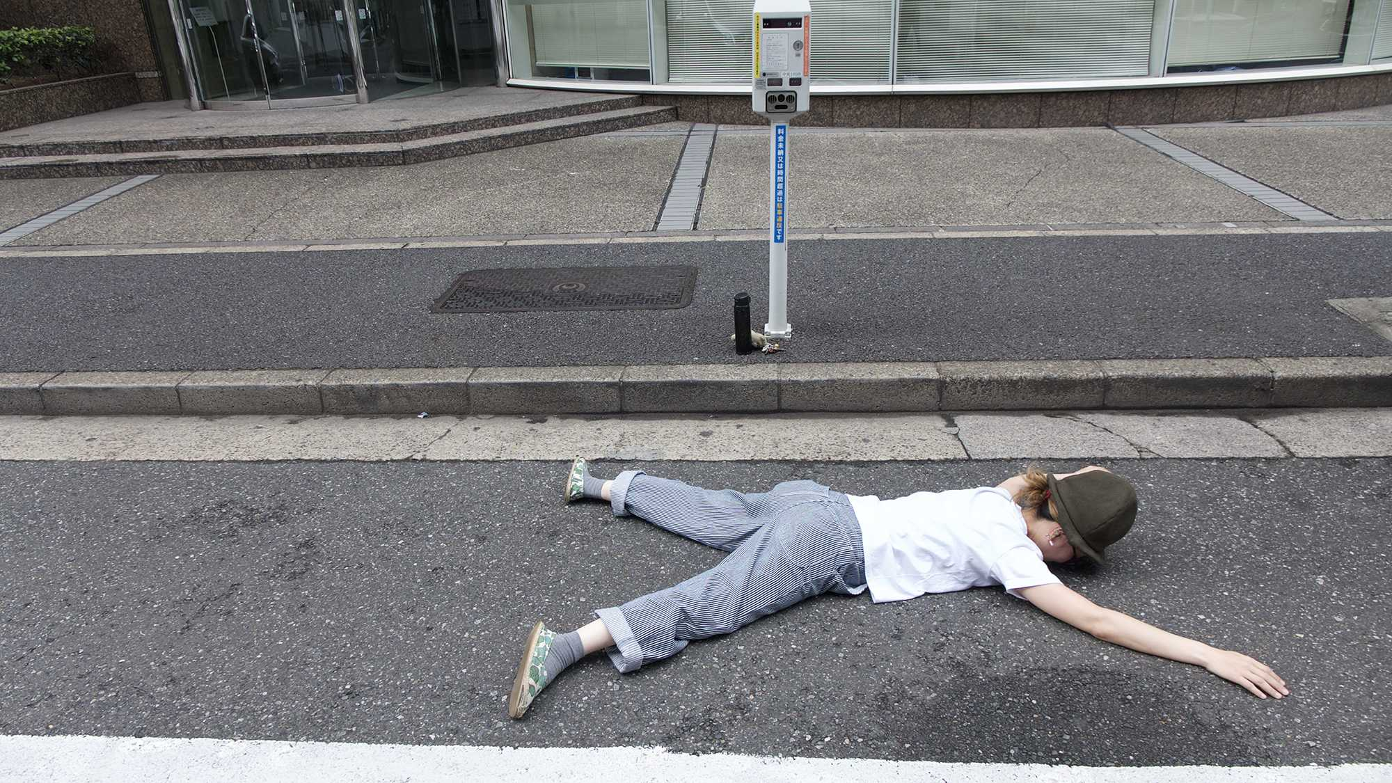 girl lying in parking space tokyo